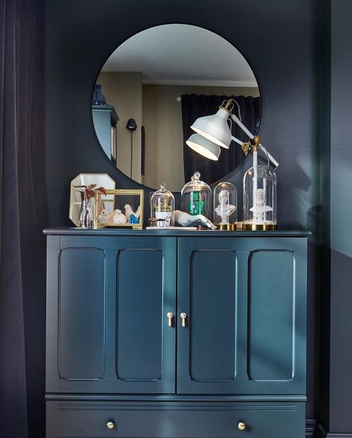 Cermin bundar, kabinet berwarna biru-hijau gelap dan benda-benda kecil dekoratif yang berada dalam kubah kaca dan kotak display.