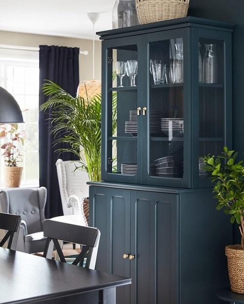 Kabinet LOMMARP berwarna biru-hijau gelap dengan pintu kaca terletak di samping meja makan, perlengkapan makan berada di belakang pintu kaca.