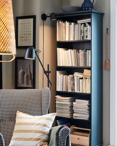Sudut baca yang nyaman dengan lampu dinding SKURUP, lampu lantai SKURUP, kursi berlengan, dan rak buku berwarna biru kehijauan.