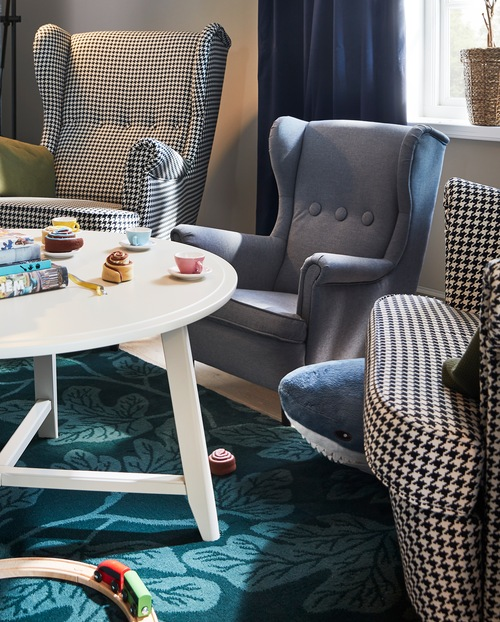 Dua kursi berlengan dan kursi berlengan untuk anak-anak terletak di dekat meja KRAGSTA bulat  berwarna putih dengan mainan di atasnya.