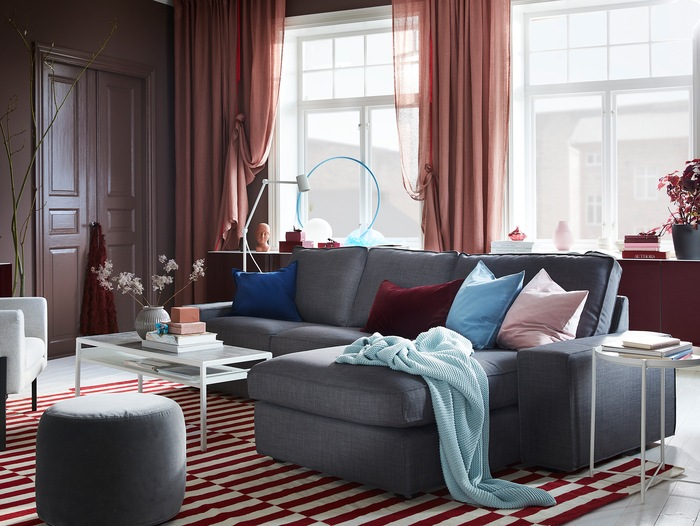 Ruang keluarga dengan tirai berwarna cokelat-merah muda, karpet berwarna merah / putih, sofa abu-abu, dan kabinet yang terpasang di dinding dengan pintu berwarna merah yang mengkilap.