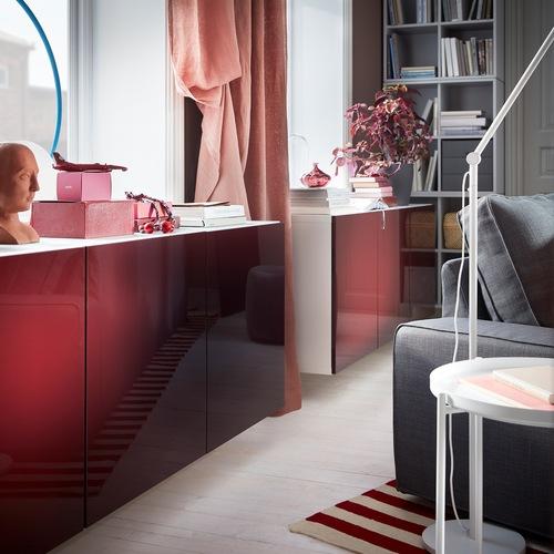 Kombinasi kabinet BESTÅ putih dengan pintu mengkilap dalam warna merah-coklat tua dipasang di dinding di bawah jendela.