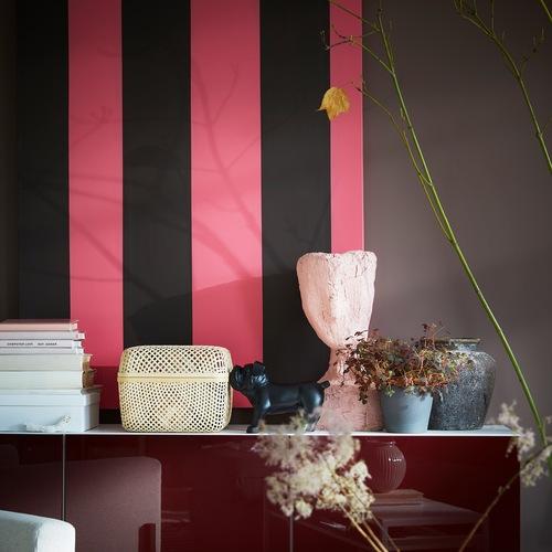 Sebuah kotak penyimpanan SMARRA dengan penutup bermaterial bambu menawarkan penyimpanan dan berada di atas kabinet putih / merah-cokelat di antara barang-barang dekoratif lainnya.
