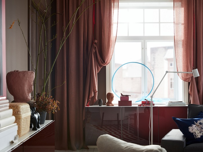Tirai LEJONGAP berwarna coklat muda-merah muda dibungkus dengan pita merah dan digantung di dekat jendela dimana cahaya bersinar dengan indah.