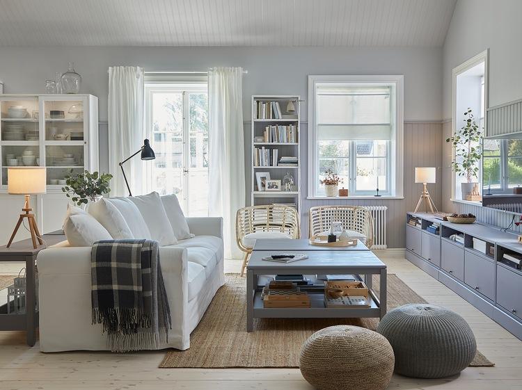 Ruang keluarga bergaya tradisional dengan sofa putih, karpet dengan material goni, dua meja tamu abu-abu, meja TV berwarna abu-abu dan dua kursi berlengan dengan material rotan.