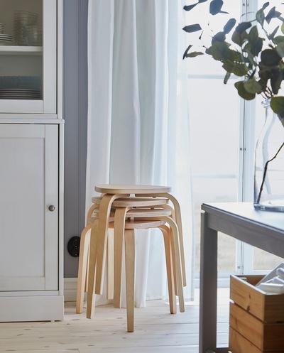 Empat kursi KYRRE dengan material kayu birch ditumpuk di dekat jendela, dan kursi-kursi tersebut menyediakan tempat duduk tambahan untuk meja makan saat diperpanjang.