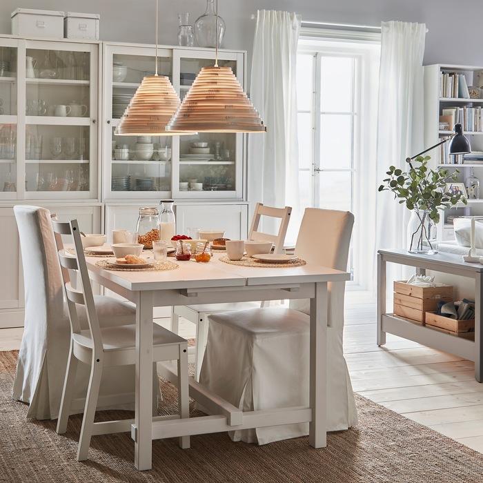 Meja makan NORDVIKEN yang dapat diperpanjang dan kursi-kursi membentuk suasana sarapan. Lampu gantung yang menyala memberikan pencahayaan yang hangat dari atas.