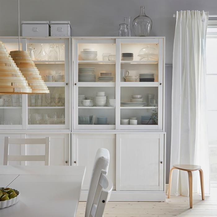 Ruang makan di mana peralatan makan dan gelas disimpan di dalam kombinasi penyimpanan HAVSTA putih dengan pintu kaca geser.
