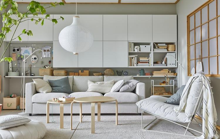 Ruang tamu yang terang dengan kursi malas HAVSTA, beberapa kabinet putih di dinding, dan lampu gantung bundar berwarna putih.