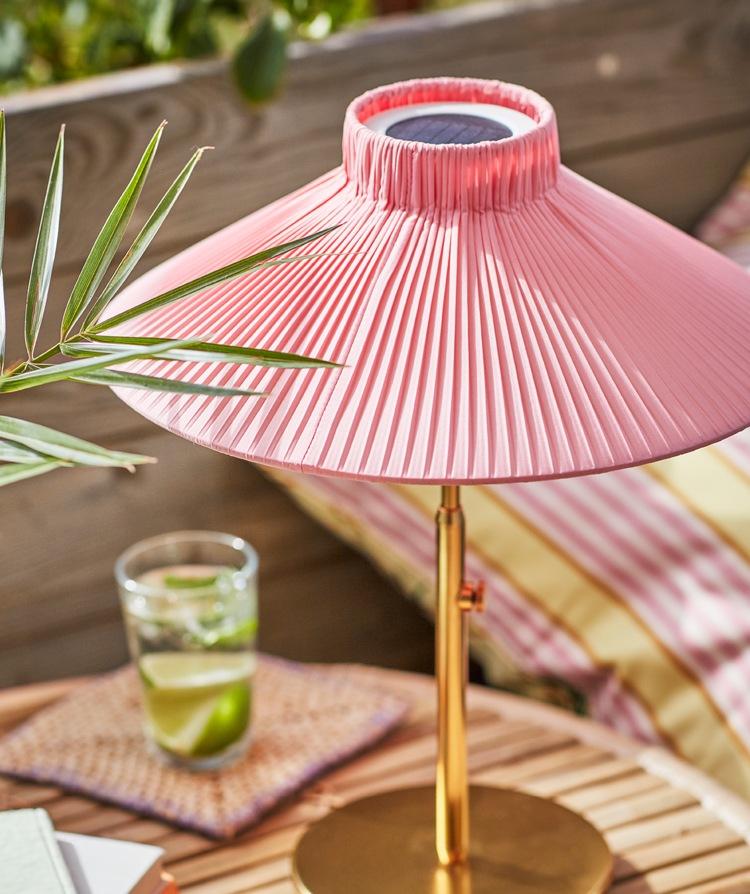Sebuah lampu meja SOLVINDEN bertenaga surya yang disinari matahari berdiri di atas meja bersama gelas berisi minuman dan pinggiran jeruk nipis.