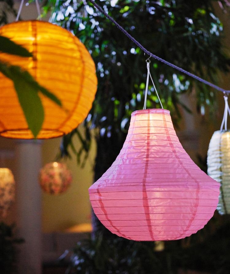 Lampu gantung bertenaga surya SOLVINDEN dalam bentuk dan warna berbeda bergantung dalam interval di taman yang asri.