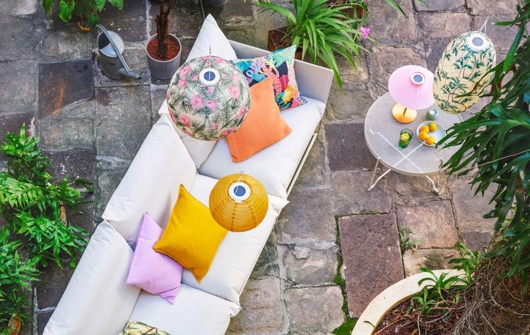 Sofa putih di teras batu alami. Bantal kursi di sofa dan lampu gantung di atasnya bercorak dan berwarna-warni cerah.