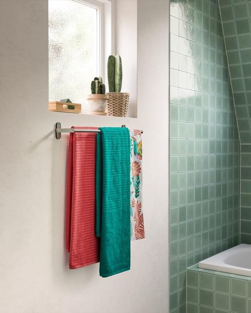 Kamar mandi dengan tema warna merah muda dan turquoise dengan wastafel dan kabinet dinding berwarna putih, keset kamar mandi merah muda, dan tirai shower dengan warna turquoise.