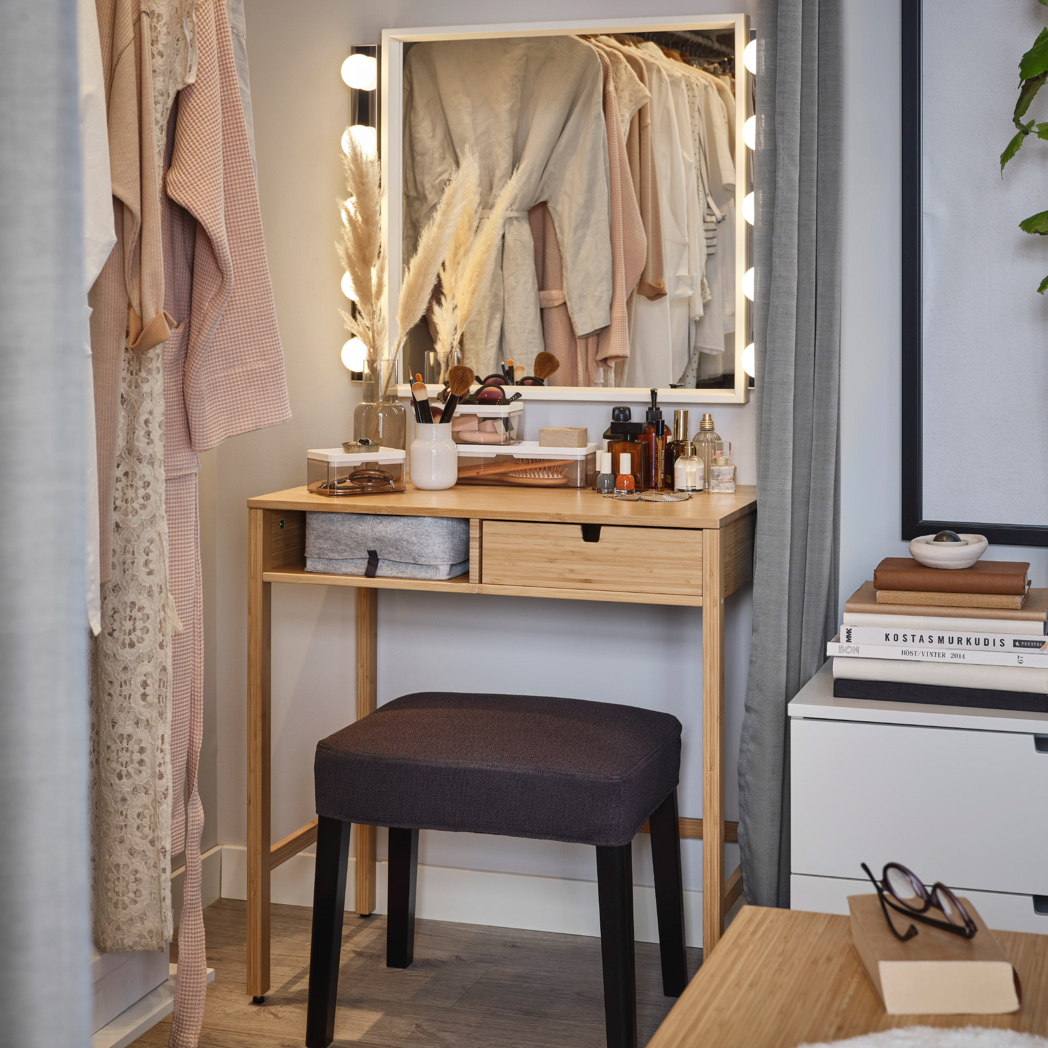 A square mirror, a dressing table in bamboo, two LED wall lamps and a dark grey stool offer a complete beauty station.