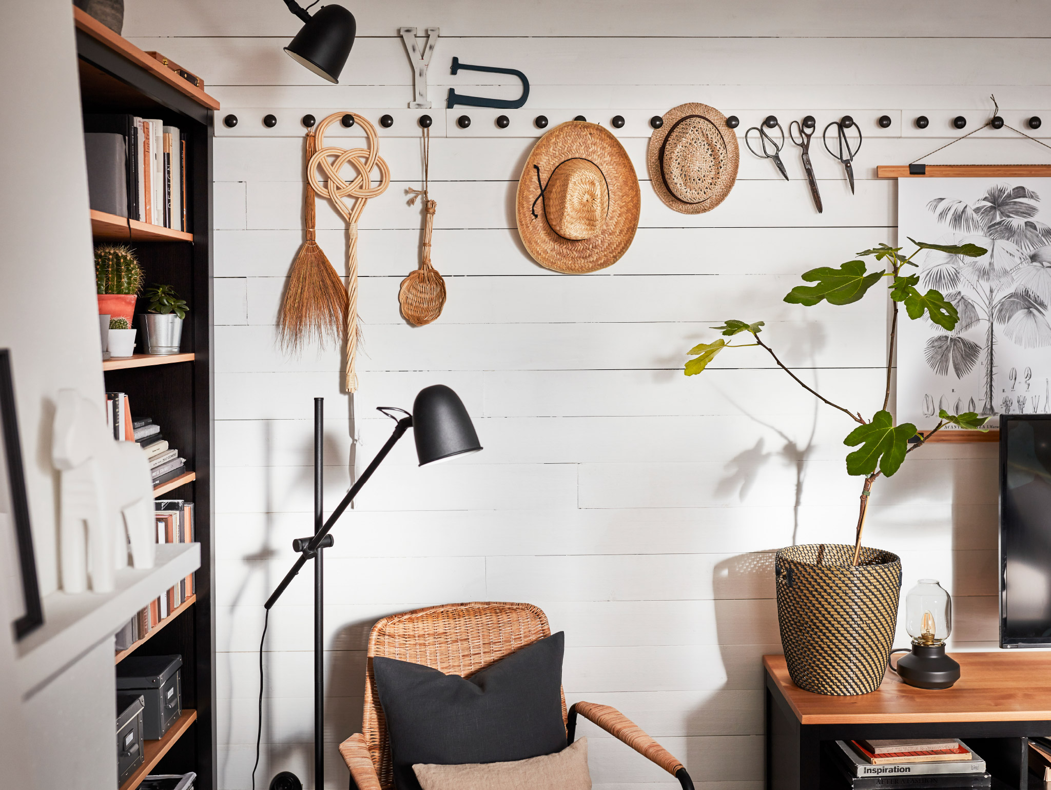 A poster with poster hanger in bamboo, decorative items and hats hang on a wall-mounted white rack with black knobs.
