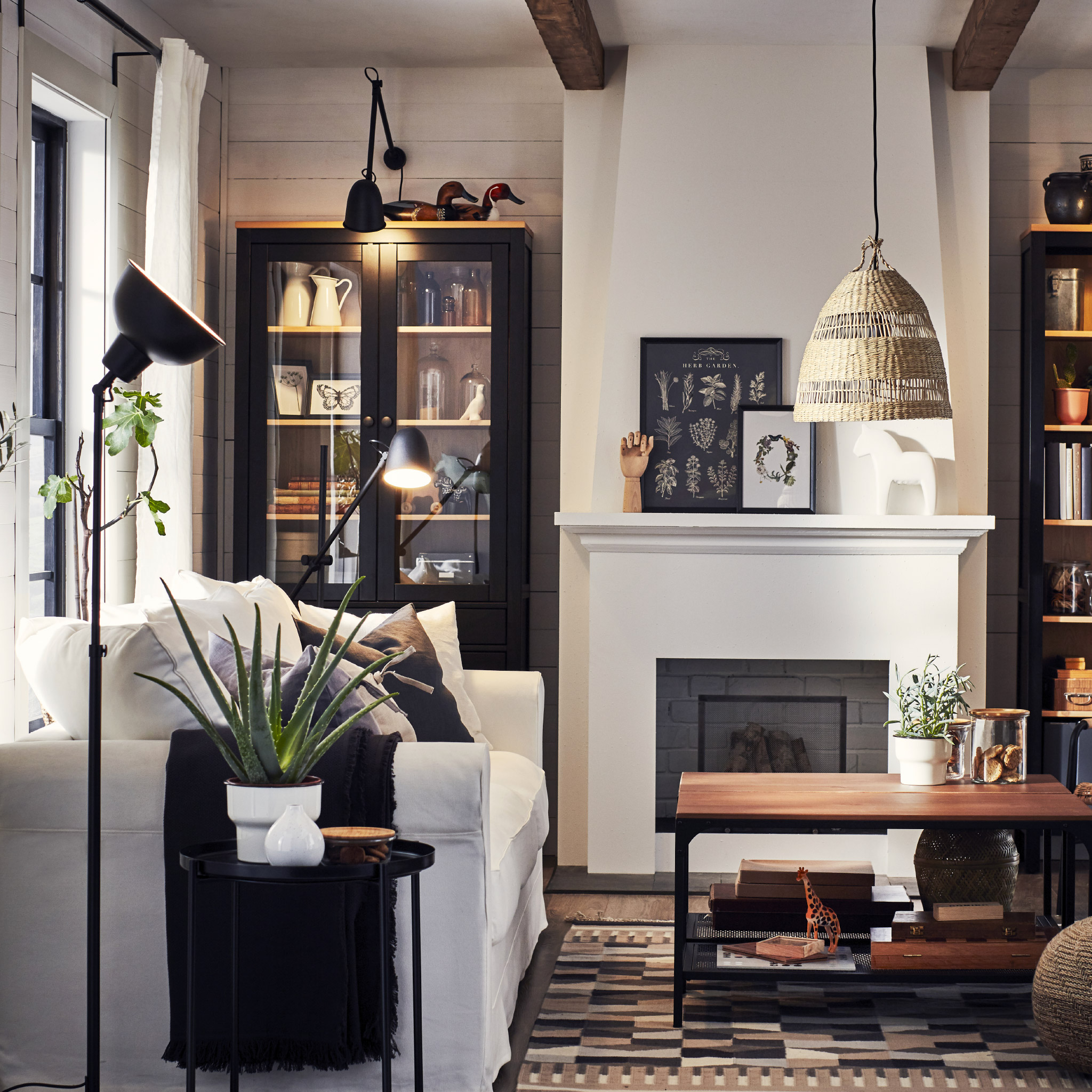 A living room with a white sofa, lamps and a side table in black, a beige-patterned rug and two coffee tables in black/wood.