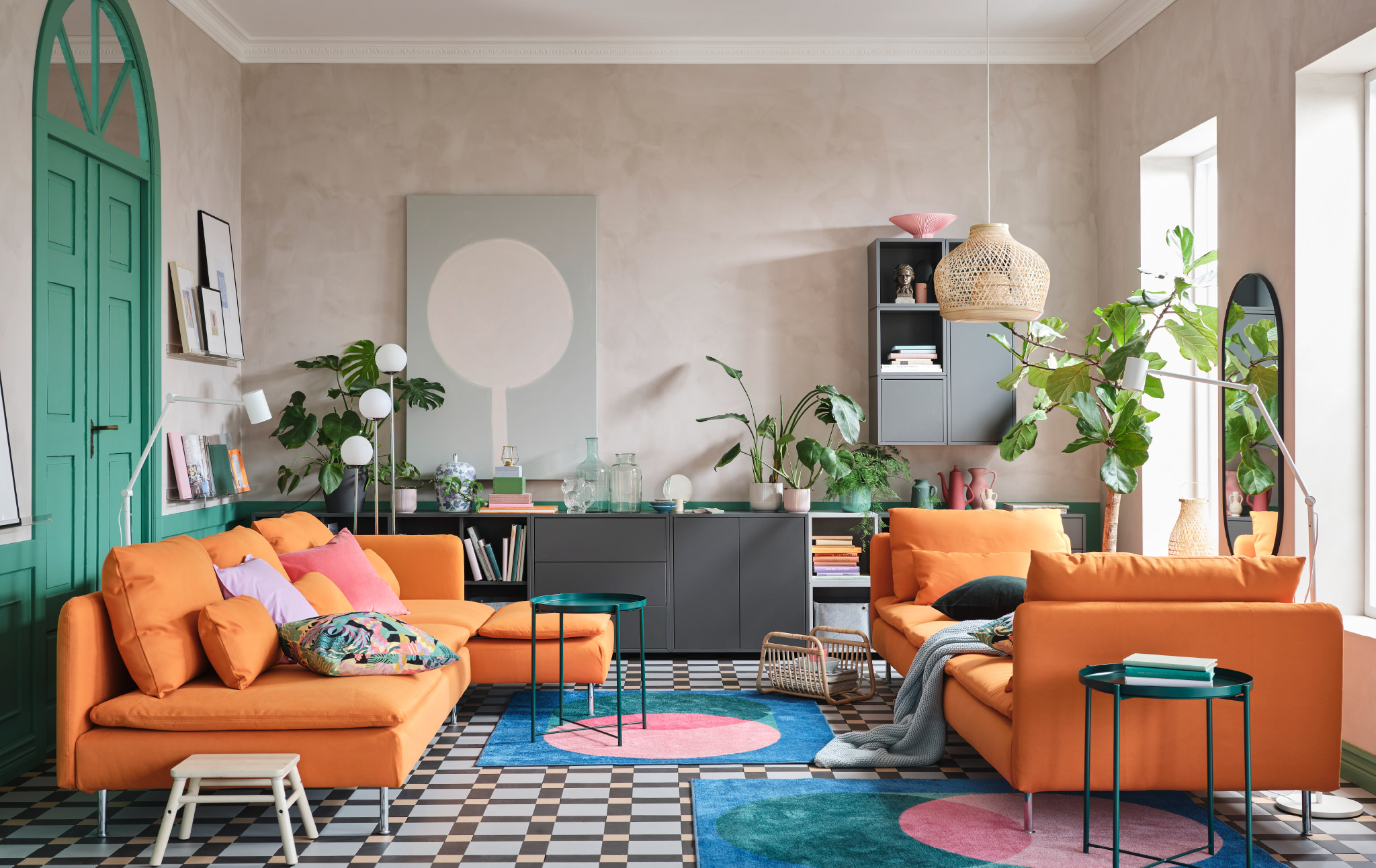 A living room with a sofa and chaise longues in orange, a cabinet combination in grey, colourful rugs and green tray tables.