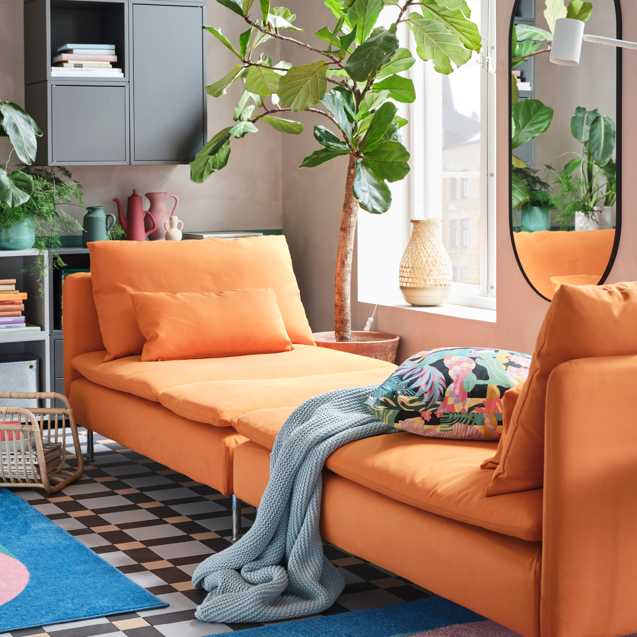 An orange 4-seat sofa with chaise longue, a green tray table, two rugs in pink/green/blue and two floor lamps in white.