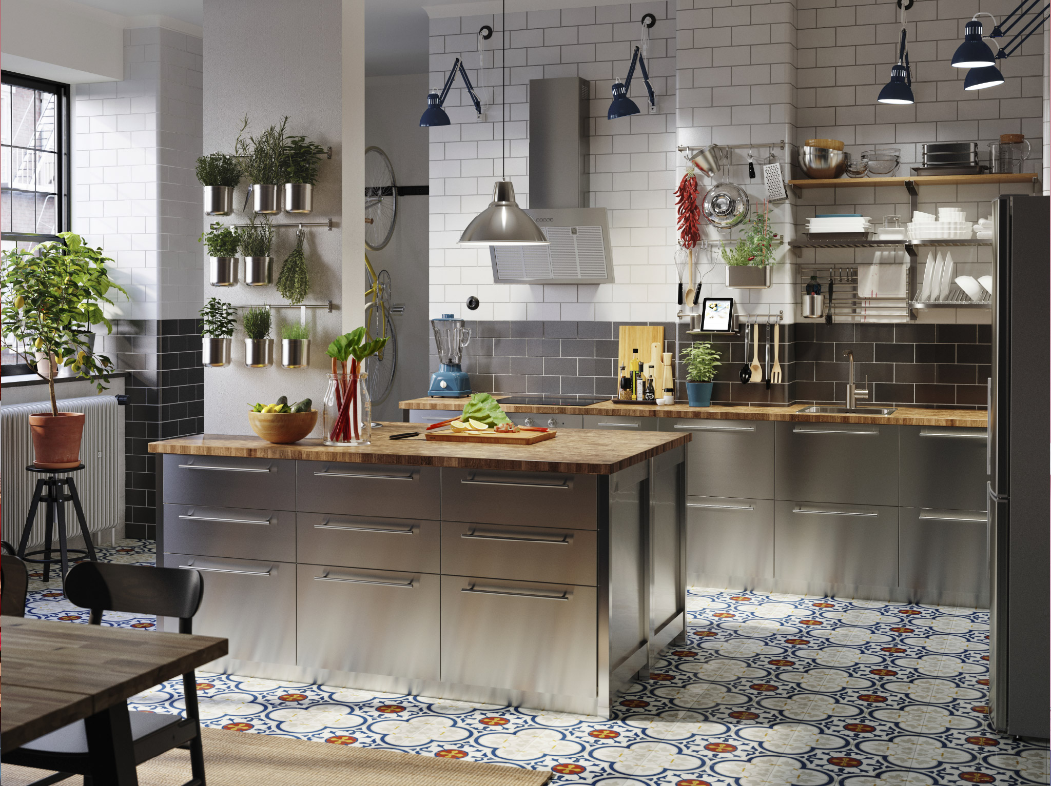 A large kitchen with fronts in stainless steel, worktops in oak/veneer, blue industrial work lamps and herbs in containers.