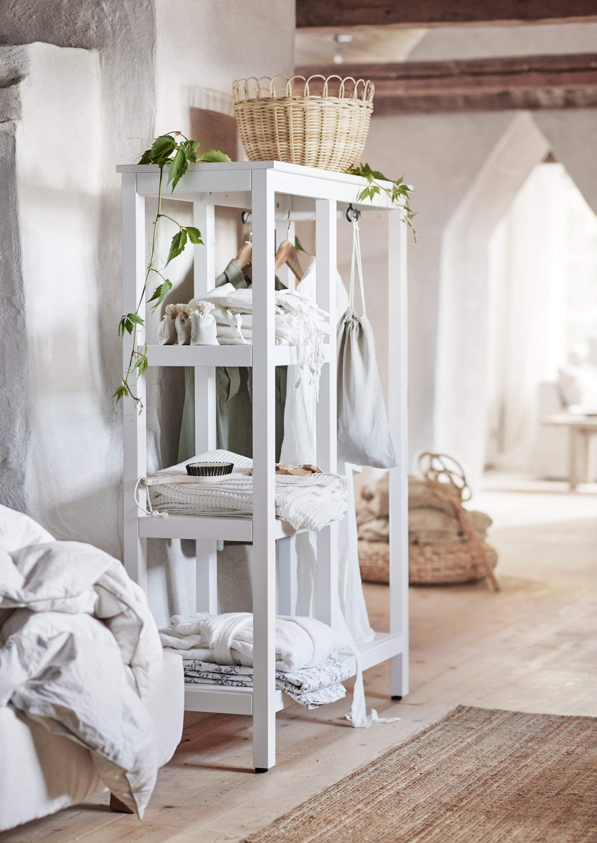 A traditional rattan basket sits on top of a white-stained open wardrobe.