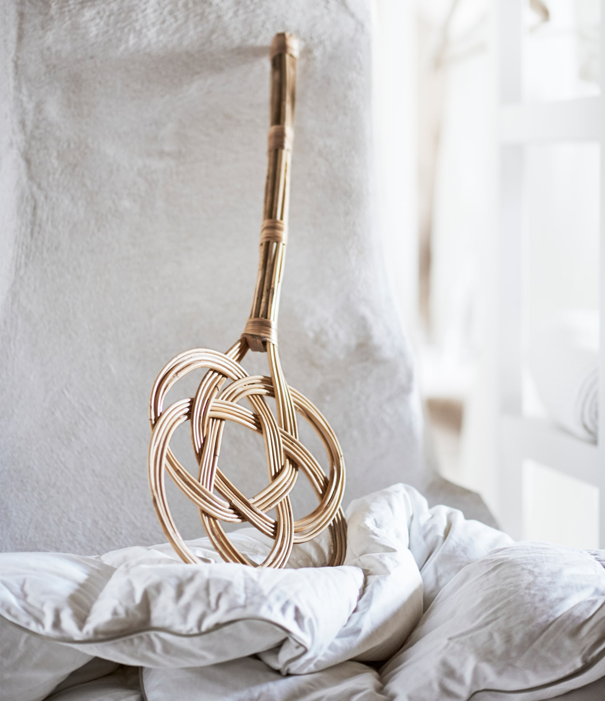 A traditional rattan carpet beater stands against a white wall.