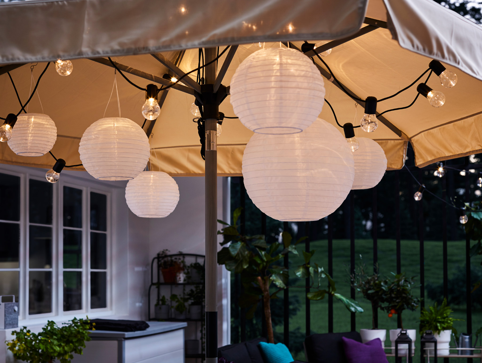 A black lighting chain and round pendant lamps hang under an open parasol, and they give a warm and cosy light.