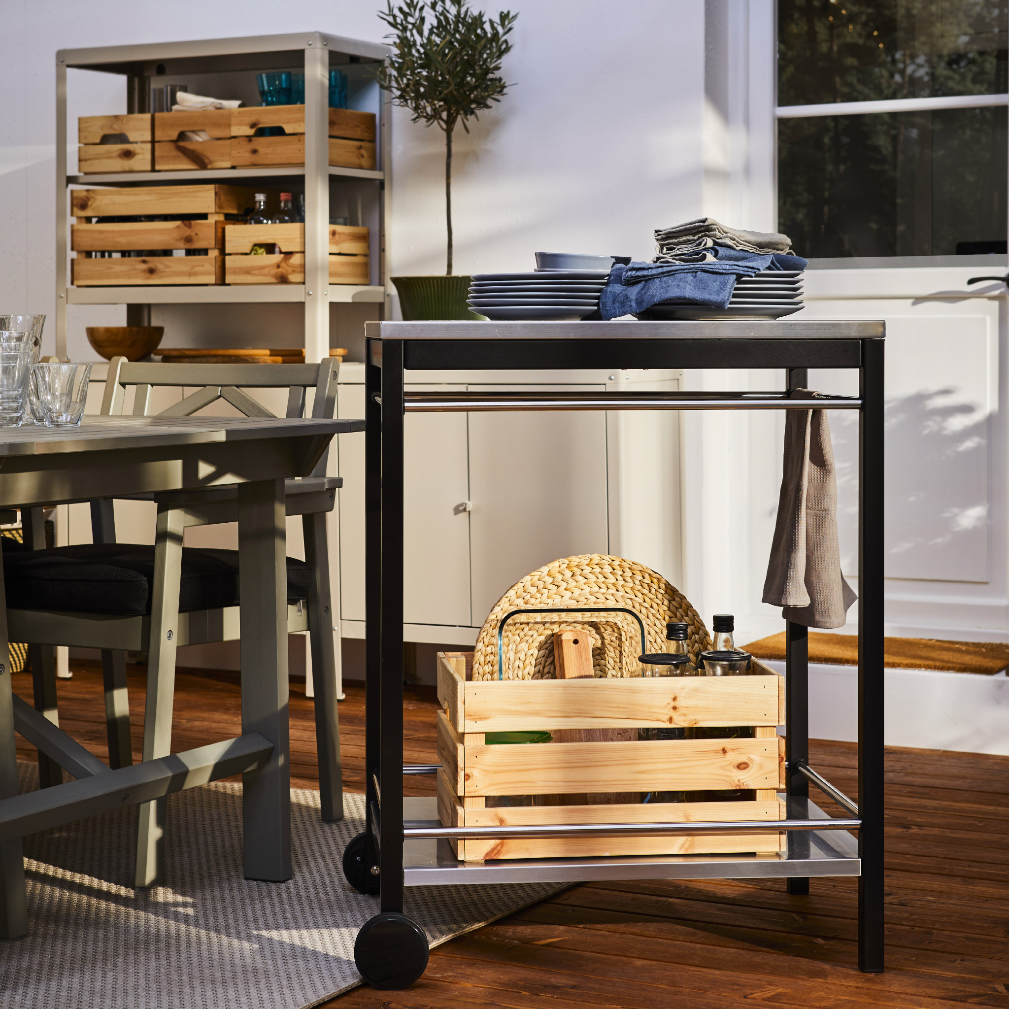 A trolley on castors in black/stainless steel holds dinnerware, towels and more, and it's standing by a dining table.