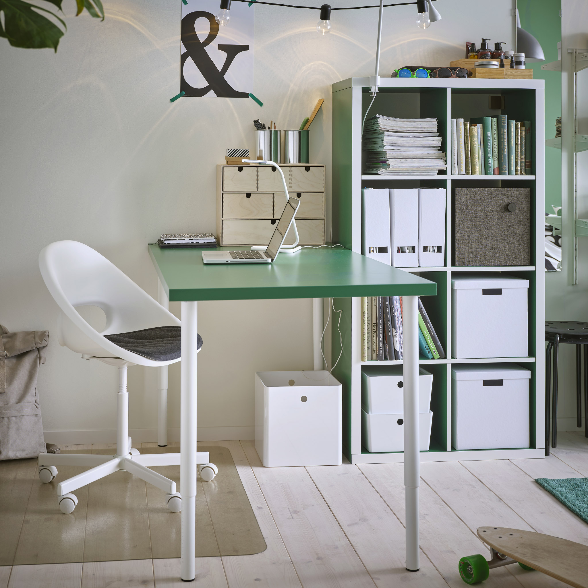 Study space with a green table with white legs, a white swivel chair, a white table lamp and a transparent floor protector.