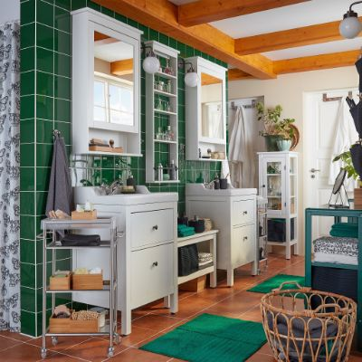 A bathroom with green tiles, two wash-basins, two mirror cabinets, a basket in rattan and two green bath mats.