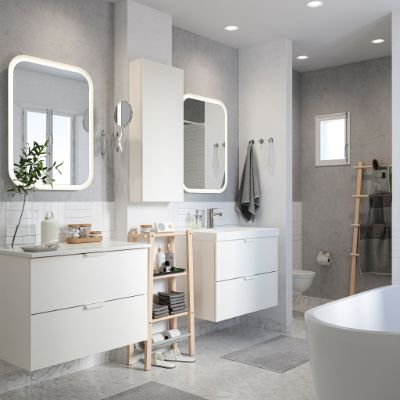 A crisp white bathroom with two wash-stands, two mirrors with integrated lighting, light grey bath mats and grey towels.