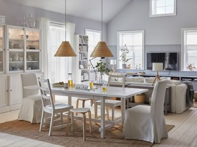 A spacious and bright dining room with a connected living room. The dining table is extended, and stools provide more seats.
