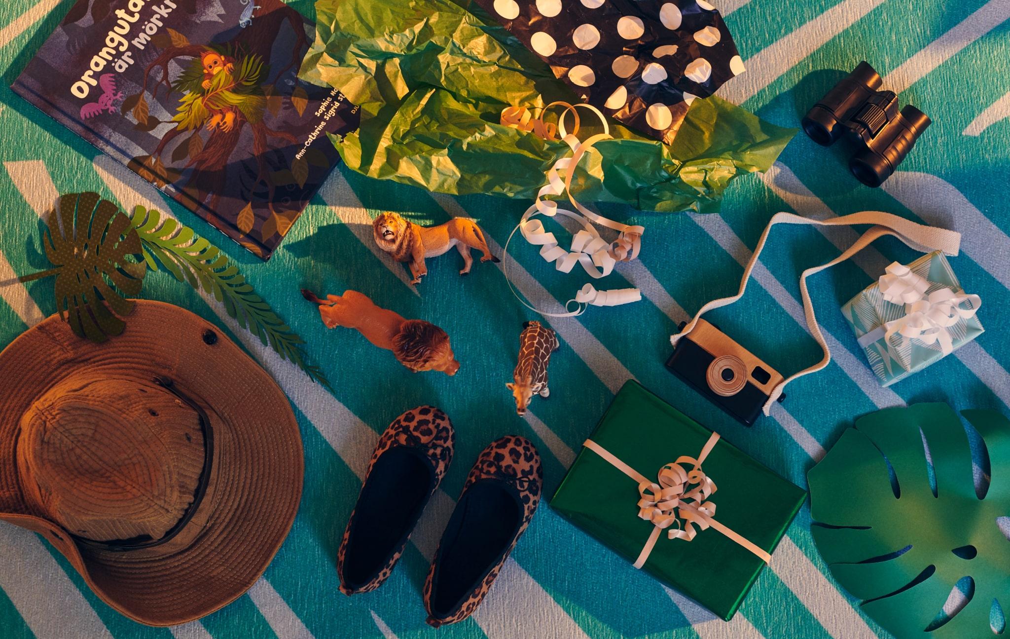 Berbagai hadiah dan mainan yang dibungkus dan yang tidak dengan tema eksplorasi dan petualangan terbaring di karpet GRACIÖS.