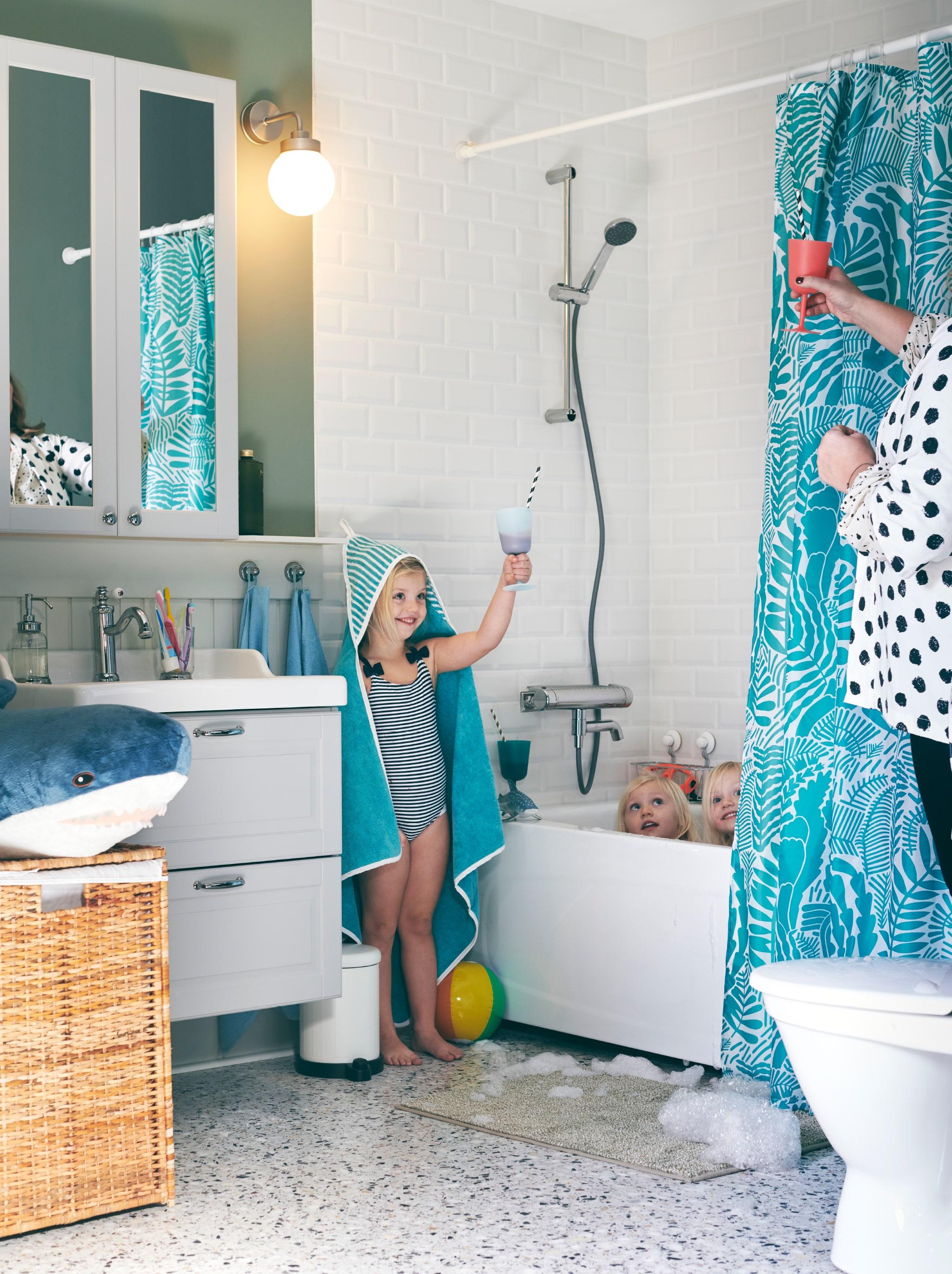 Kamar mandi dengan tiga anak perempuan di dalamnya. Salah satu dari mereka, terbungkus handuk RÖRANDE, bersulang bersama ibunya.