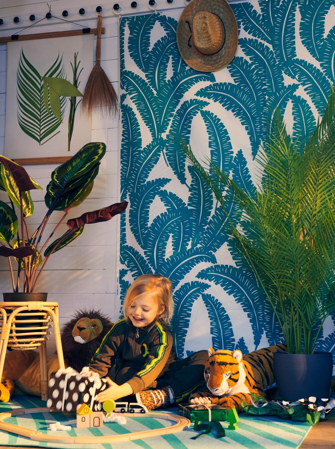 Anak perempuan memegang hadiah yang dibungkus di ruangan tempat tanaman, kain UGGLEMOTT di dinding dan karpet GRACIÖS yang menciptakan suasana hutan.