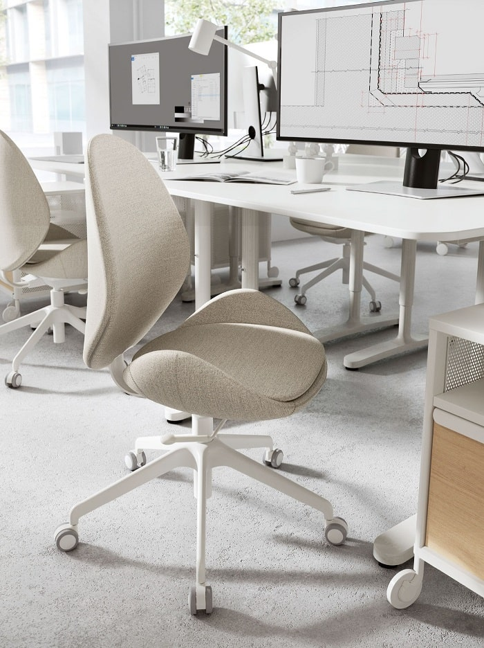 A HATTEFJÄLL office chair with beige fabric cover positioned in front of a white desk that has a computer on it.