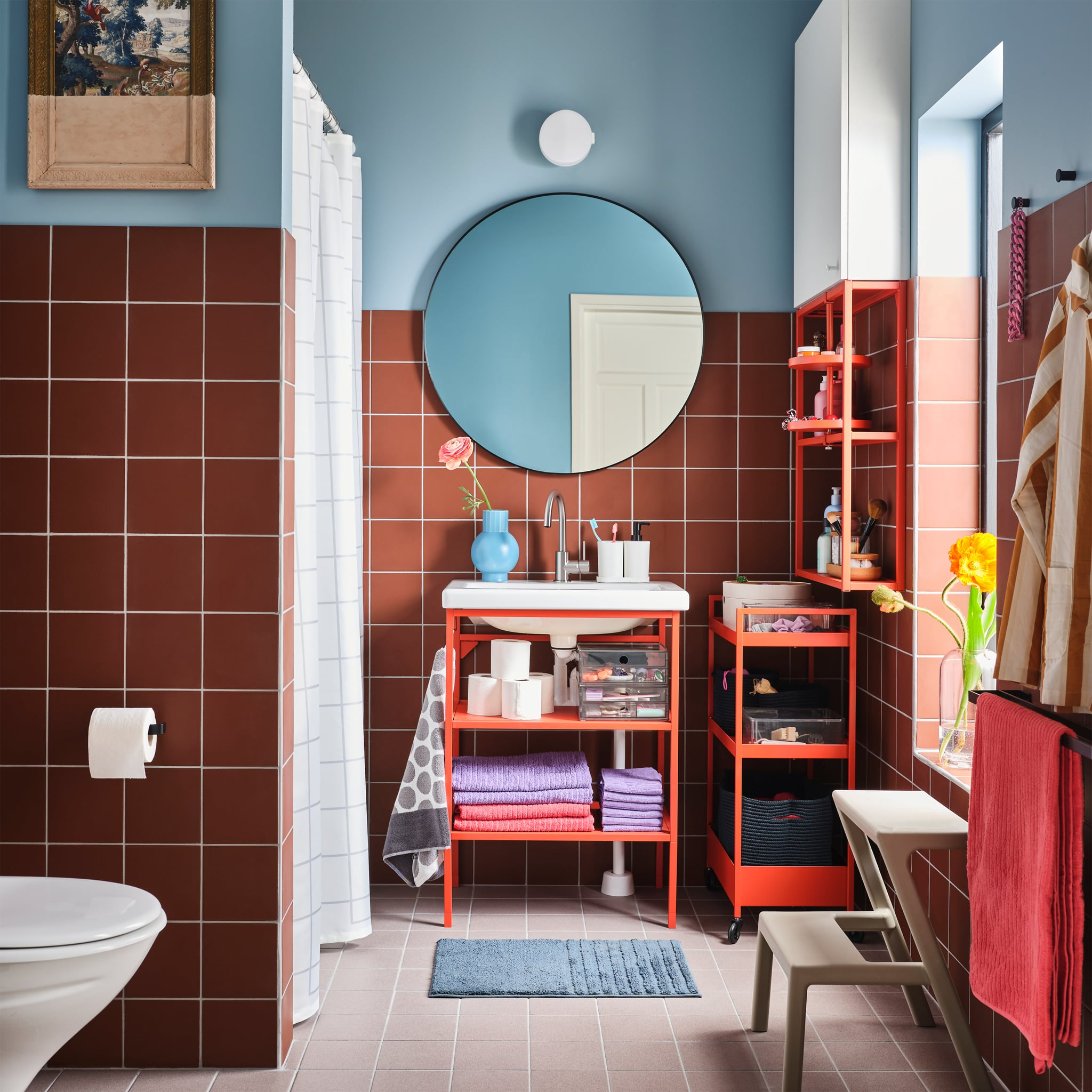 Bathroom with bathroom furniture and a trolley in red-orange, a round mirror, light red/purple towels and a beige step stool.