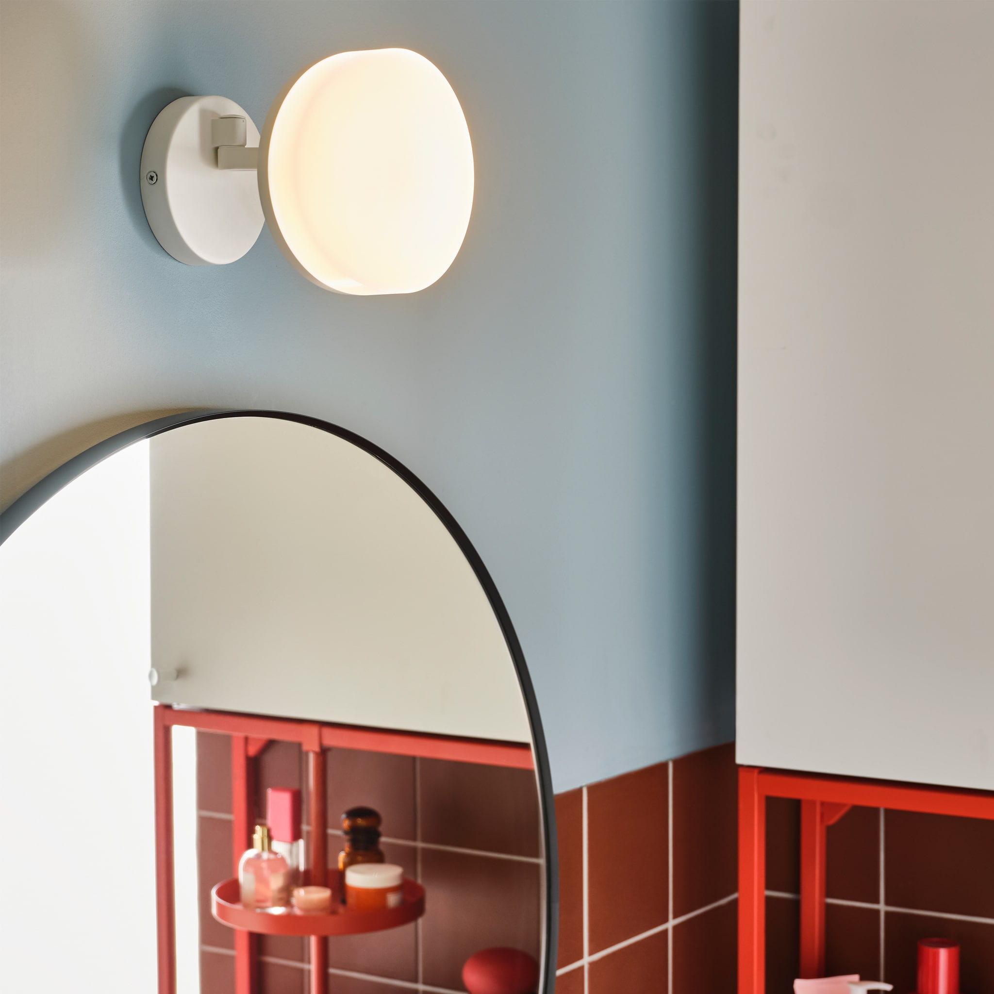 A white wall lamp with swing arm is wall-mounted above a round mirror. A white cabinet and a red-orange shelf are beside.