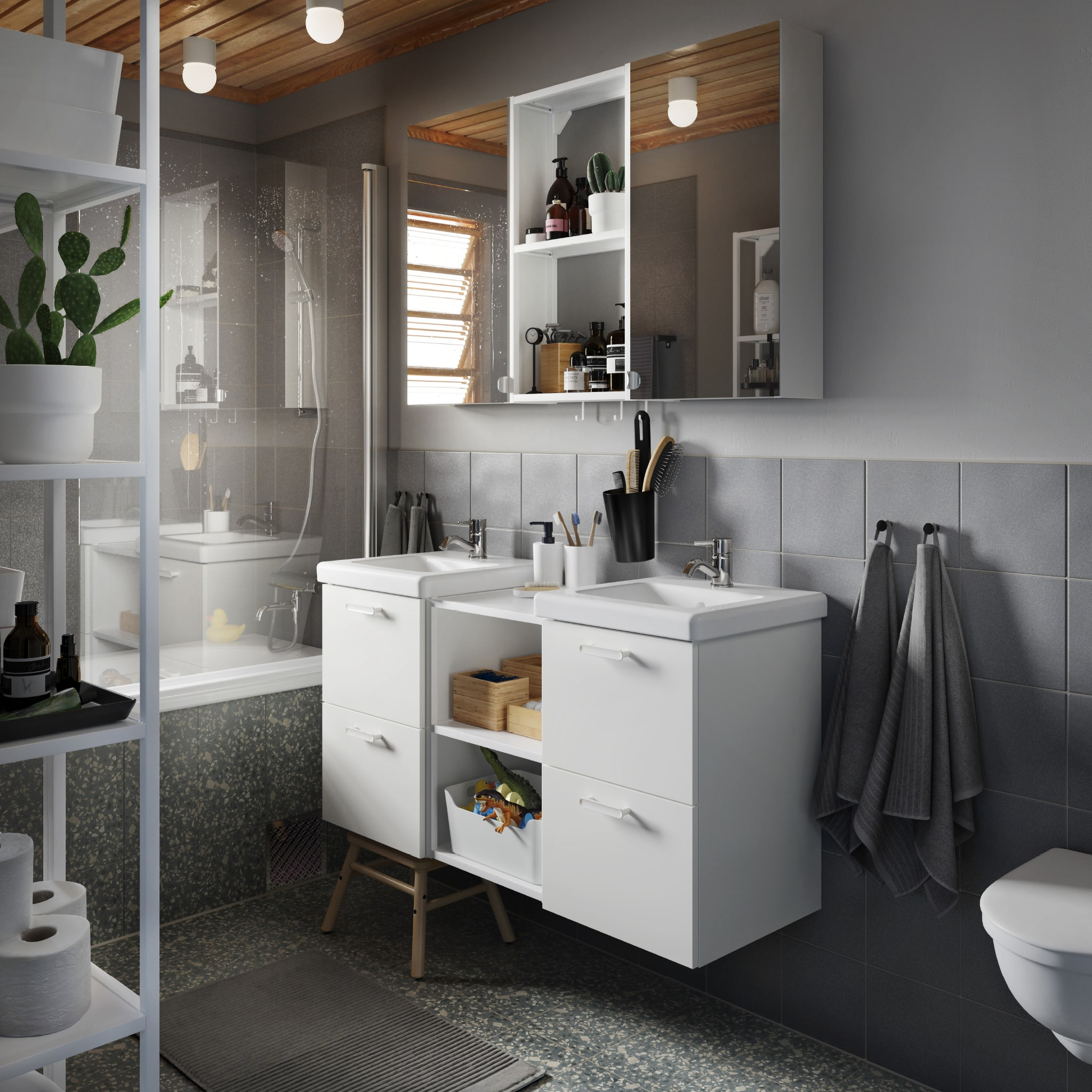 A grey bathroom with a wash-stand/wash-basin in white, a cabinet with mirror doors and bath towels and a bath mat in grey.