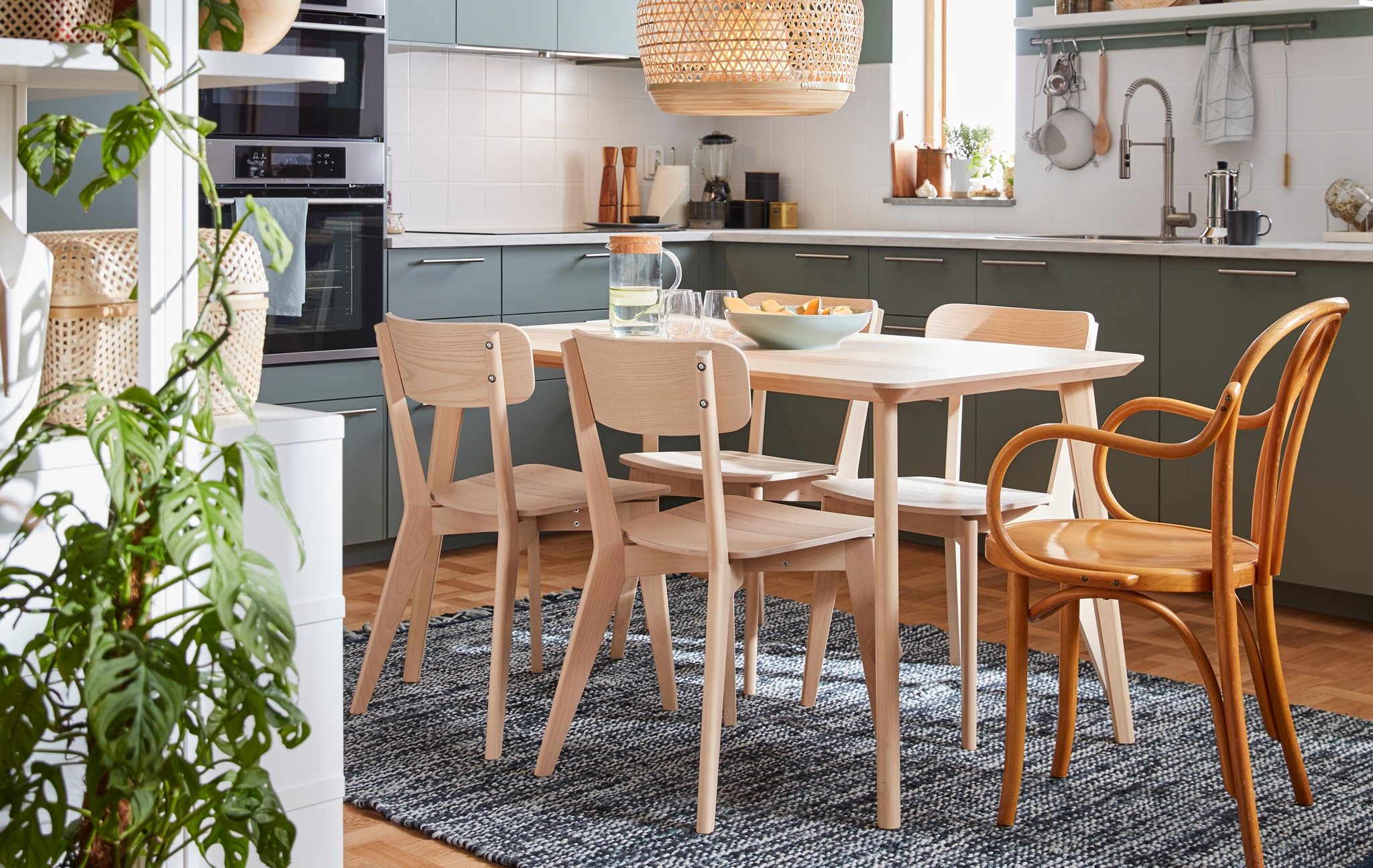 A kitchen with an IKEA chair from the 60's, a dinner table and four chairs from the LISABO series made from birch wood.