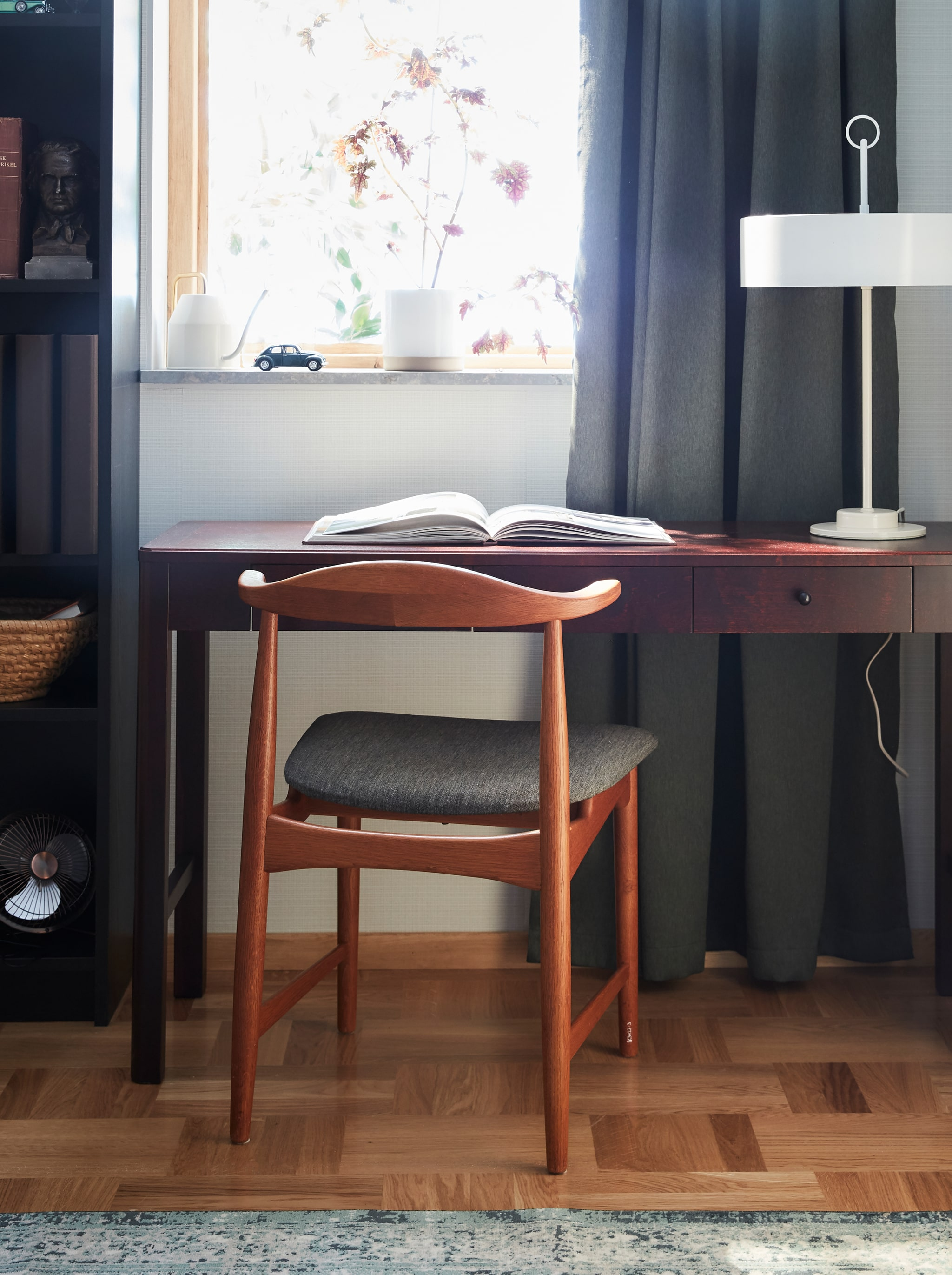 The chair DANSKE in oak with a textile seat designed for IKEA in the 60's, standing in front of a desk in dark wood.