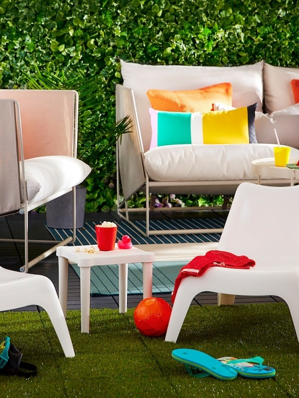 Outdoor furniture consisting of sofa, and armchair, smaller children's chairs and table with cushions and various items.