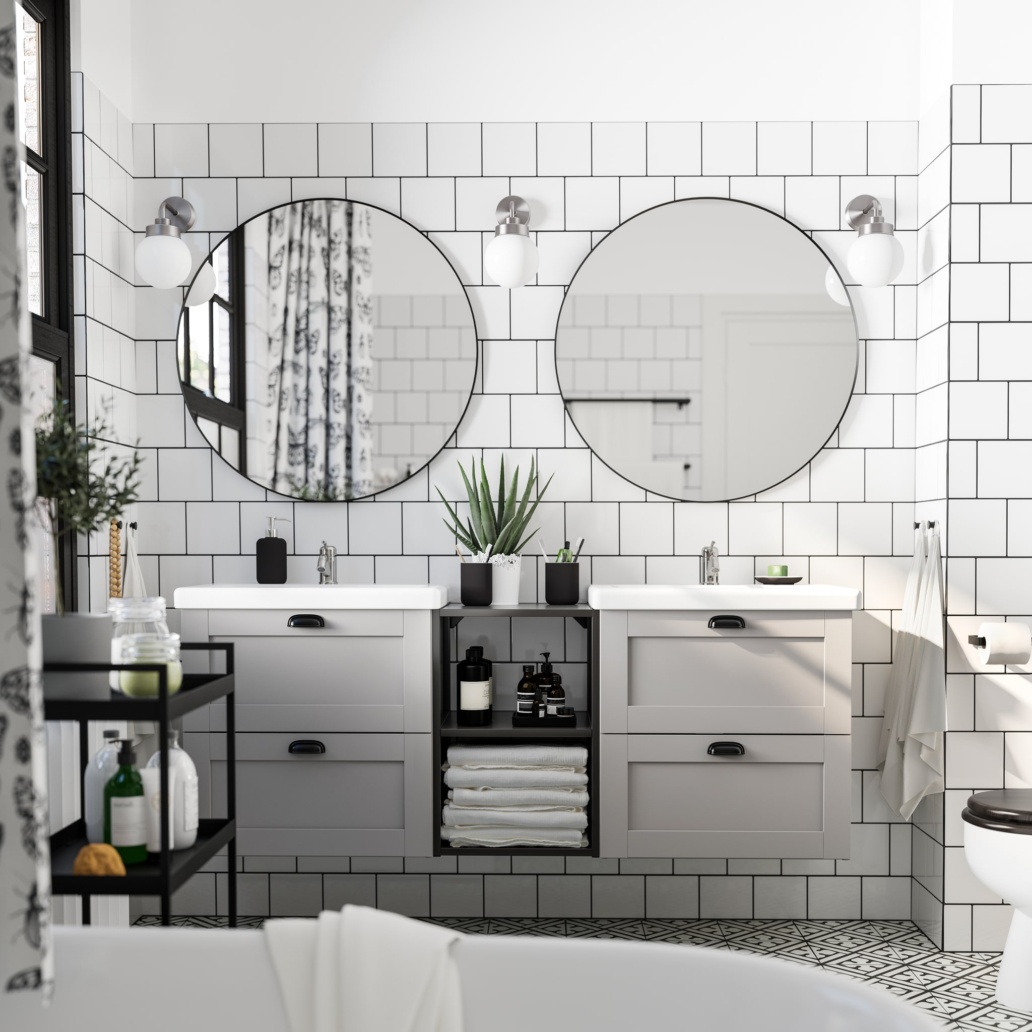 White-tiled bathroom with two round mirrors, two wash-stands/wash-basins in grey/white, a black trolley and three wall lamps.