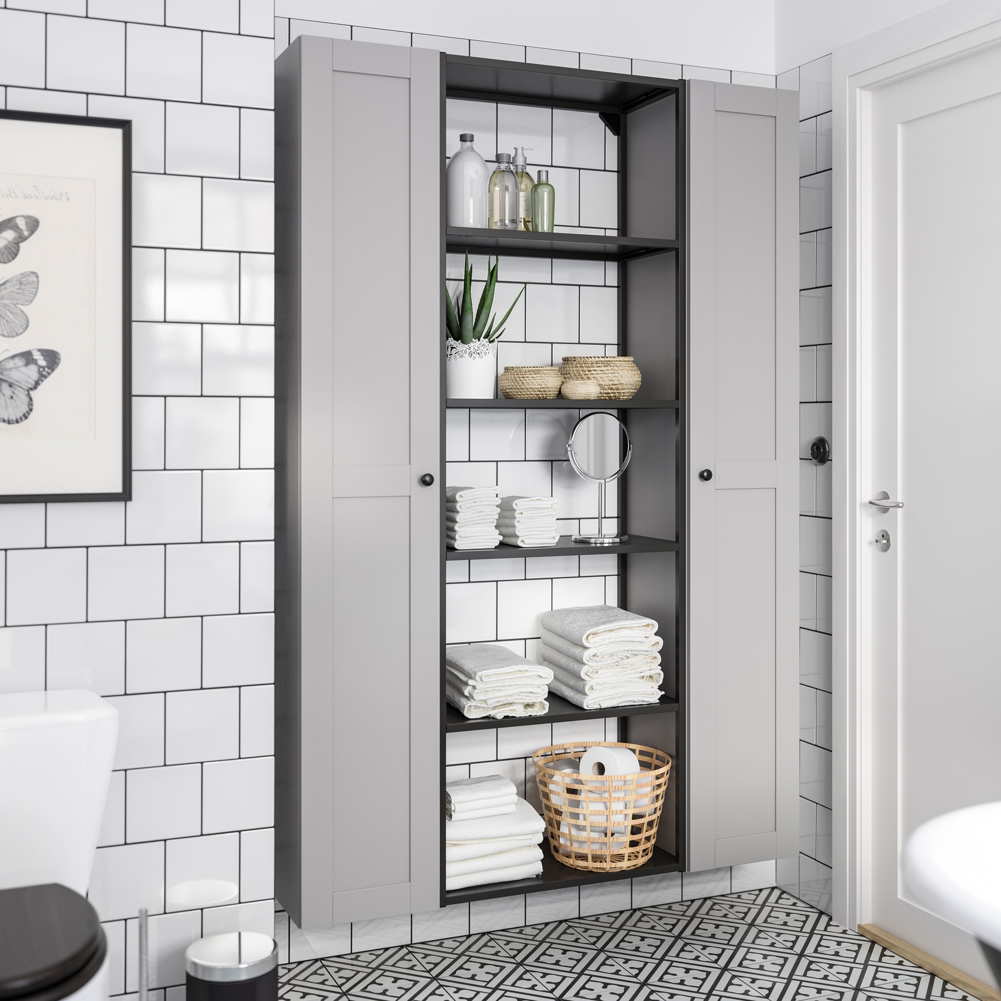 White-tiled bathroom with a storage unit that consists of two grey high cabinets and a frame with shelves in anthracite.