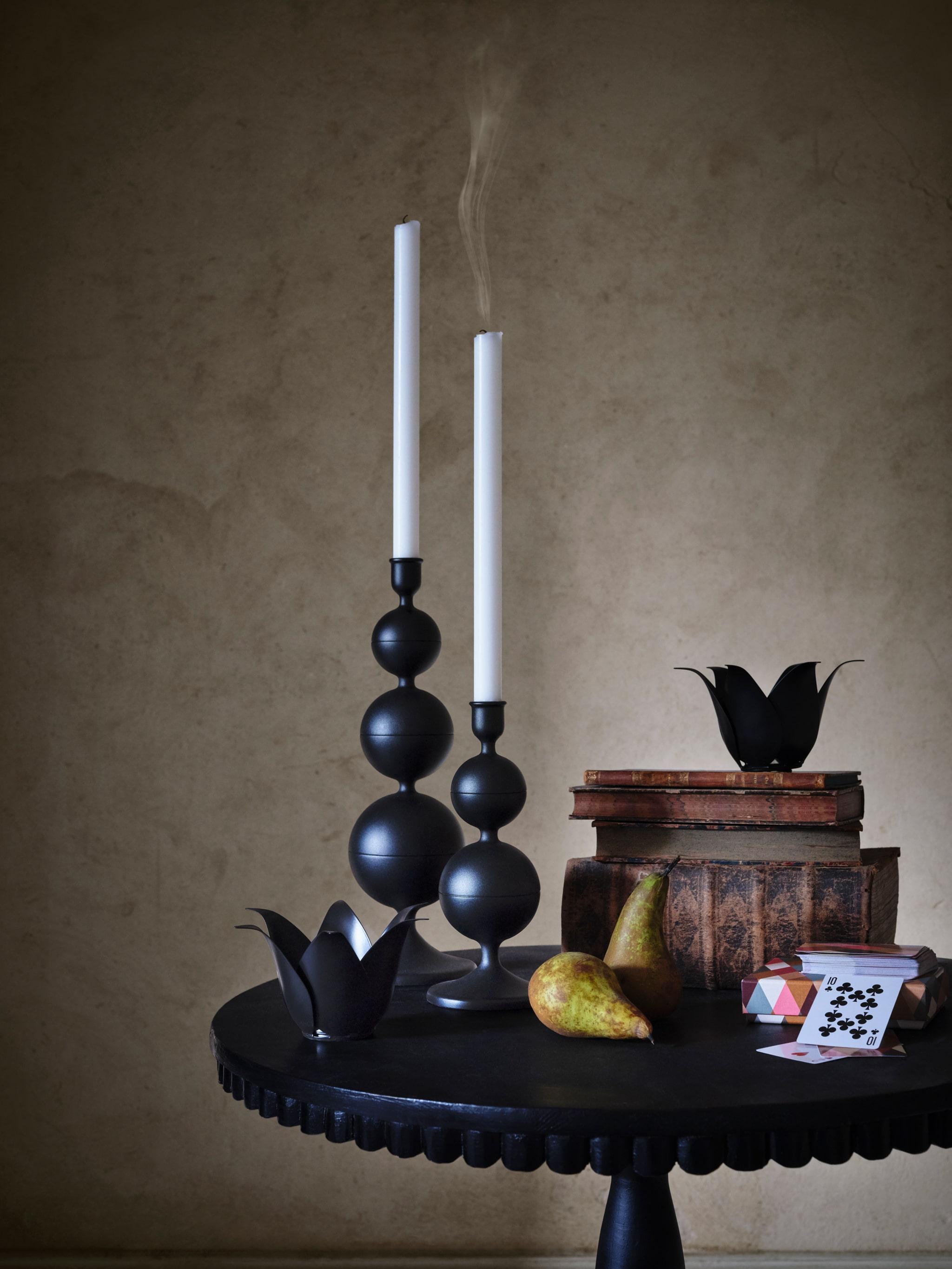 Dua tempat lilin DEKORERA warna hitam berdiri di atas meja hitam, dengan pir dan tumpukan buku di sebelahnya.